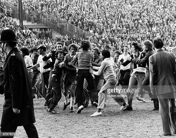 Sheffield United fans mob Steve Finneston as he tries to leave the football pitch