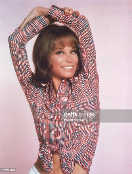 Studio portrait of American actor Mary Tyler Moore, wearing a red, white and blue striped shirt tied at the waist and smiling with her arms over her...