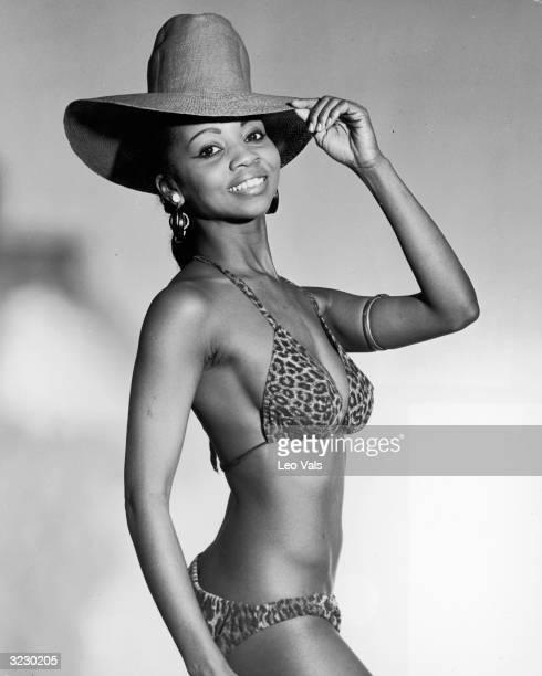 Studio portrait of an AfricanAmerican woman wearing a leopard print bikini and a wide brimmed straw hat