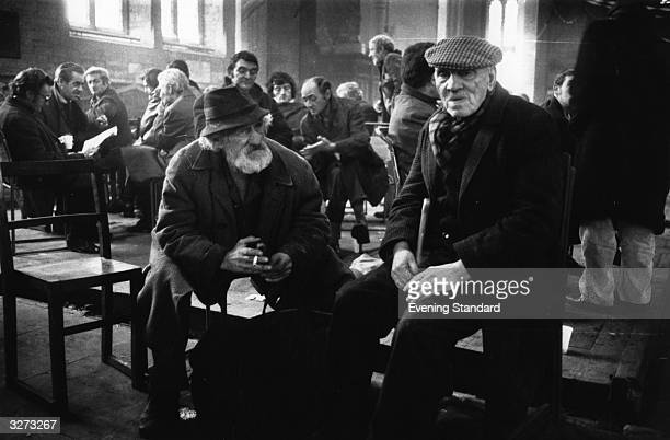 Ted Hill and Jim Robertson with other homeless people keeping warm at St Mary's Church in Lambeth