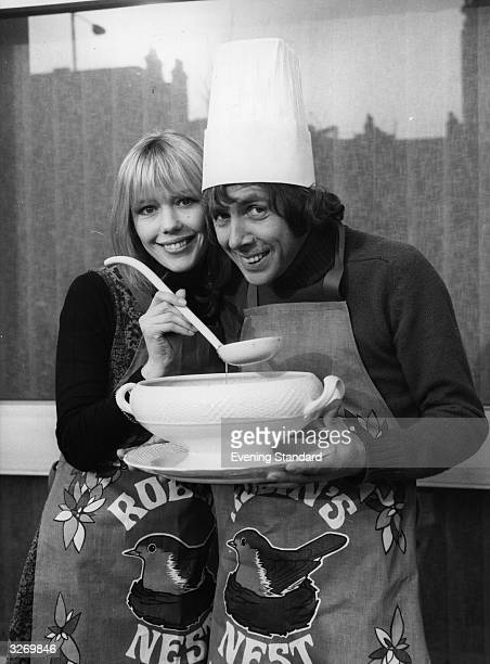 Tessa Wyatt and Richard O'Sullivan, on the set of the British TV comedy series 'Robin's Nest', wearing pinafores bearing the show's name, and holding...
