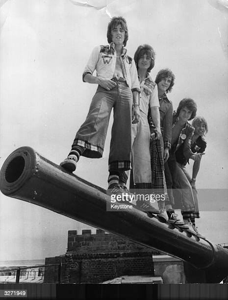 Top Scottish popsters the Bay City Rollers Woody Wood Eric Faulkner Alan Longmuir Les McKeown and Derek Longmuir on the barrel of a centuryold cannon...