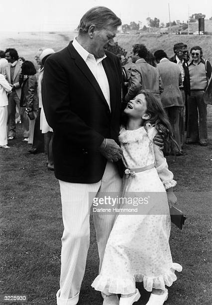 Full-length image of American actor John Wayne with his arms around his daughter, Aissa, who is smiling up at him. Behind Wayne and his daughter are...