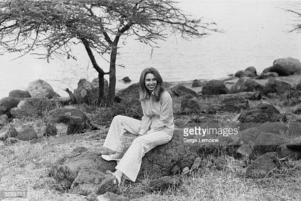 Princess Anne Elizabeth Alice Louise sitting on a rocky beach by a lake while in Ethiopia