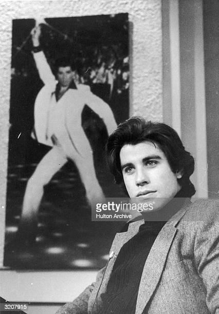 Actor John Travolta sits beside a promotional poster of himself from director John Badham's film 'Saturday Night Fever' during a television interview