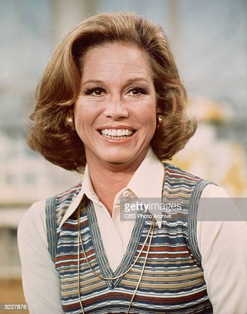 American actor Mary Tyler Moore smiling in a headshot still from the television series, 'The Mary Tyler Moore Show'. She is wearing a white blouse...