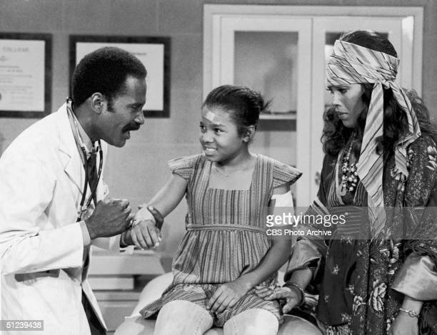 Circa 1978 American actor Bob Delegall examines a scrape on the arm of child actor and singer Janet Jackson as American actor Ja'net DuBois looks on...
