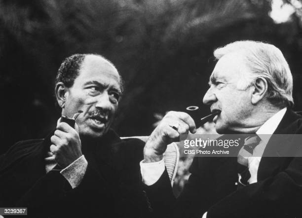 American broadcast journalist Walter Cronkite and Egyptian president Anwar el Sadat sit together and smoke pipes