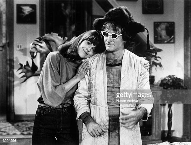 American comedian and actor Robin Williams wearing a woman's bathrobe furry hat and sunglasses being hugged by American actor Pam Dawber in a still...