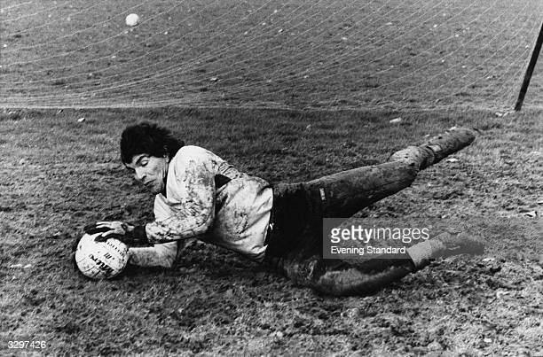Chelsea goal keeper Peter Bonetti takes a muddy dive