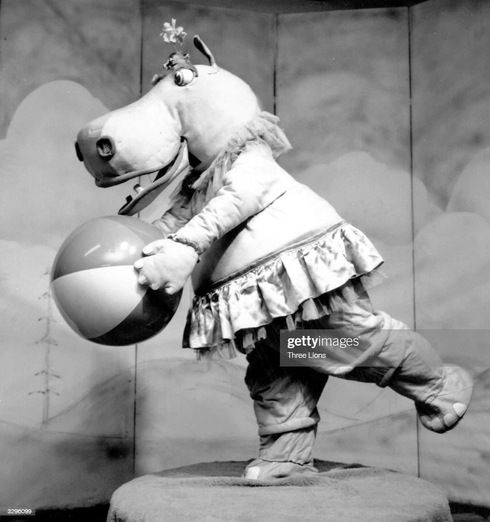 A happy hippopotamus plays with a beach ball.