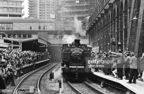 Steam train arrives at a station to a huge crowd. The modern towers of the Barbican Centre stand in the background.