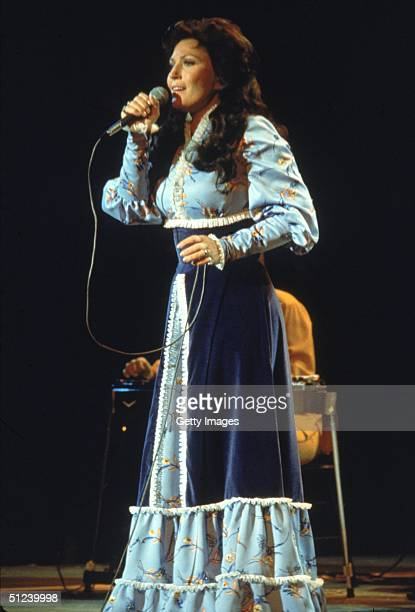 Circa 1980 American country singer and songwriter Loretta Lynn performs on stage wearing a long dress