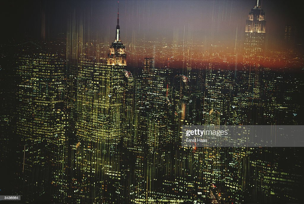 Empire State Building in New York surrounded by the lights of the city at night. Image Appears - HaasCD