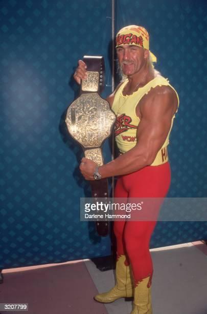 Fulllength image of American wrestler Hulk Hogan displaying his championship belt Hogan wears a costume consisting of a yellow 'HOGAN' bandana a...