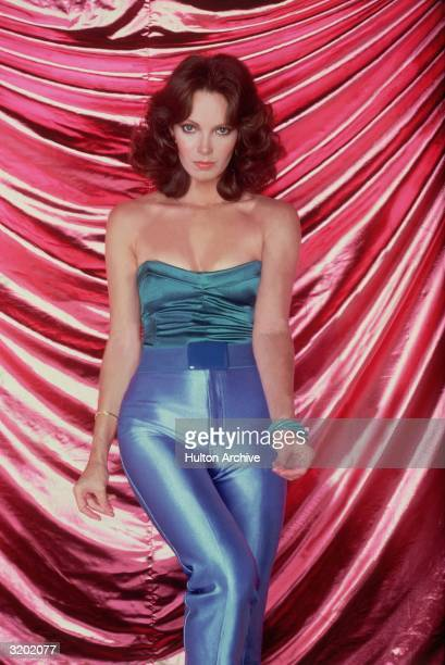 Portrait of American actor Jaclyn Smith wearing shimmery periwinkle pants and a sleeveless turquoise top standing in front of a satiny pink backdrop...