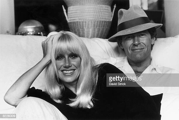 Portrait of American actor Suzanne Somers and her husband Canadian television show host Alan Hamel sitting on a sofa in their home Hollywood...