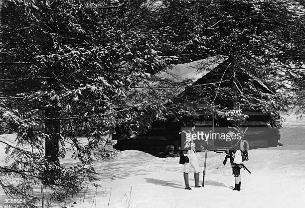 Two men dressed as colonial soldiers standing outside one of the reconstructed log cabins in Valley Forge National Historical Park Pennsylvania The...