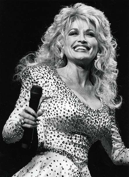 Volume 2, Page 115, Picture, 3, Country & western singer and film actress, Dolly Parton, smiling on stage during a concert