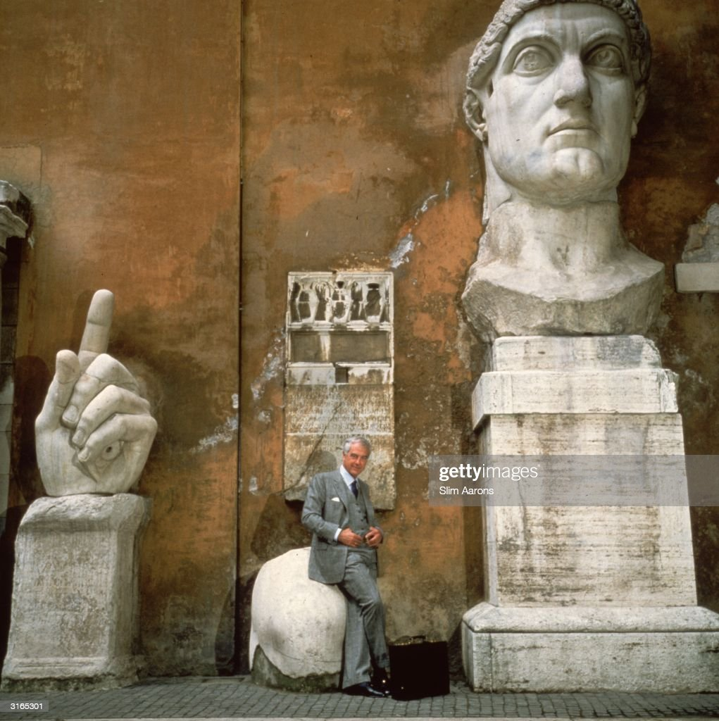 Aeronautical engineer, Dr Elio de Sabata sits on a fragment of the great statue of Constantine the Great in the courtyard of the Palazzo dei Conservatori, Rome.