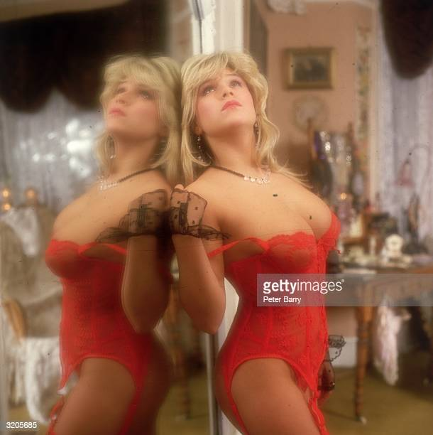 British glamour model, Samantha Fox, posing in a red basque and leaning against a mirror. She later enjoyed brief success as a pop star.