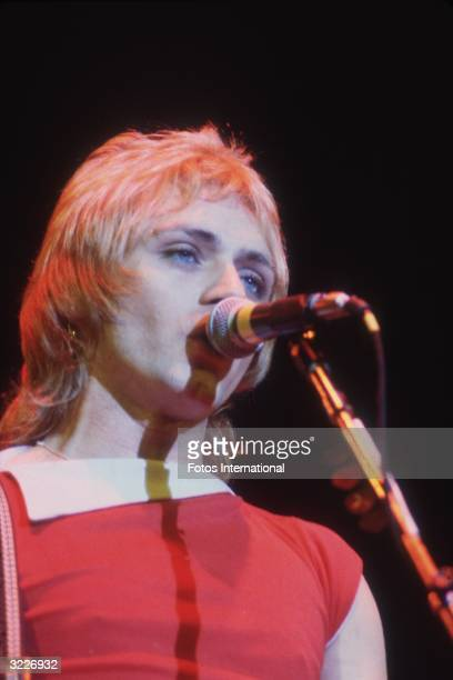 Headshot of American rock musician Benjamin Orr bassist and singer from the rock group the Cars singing at a microphone on stage He wears a red...