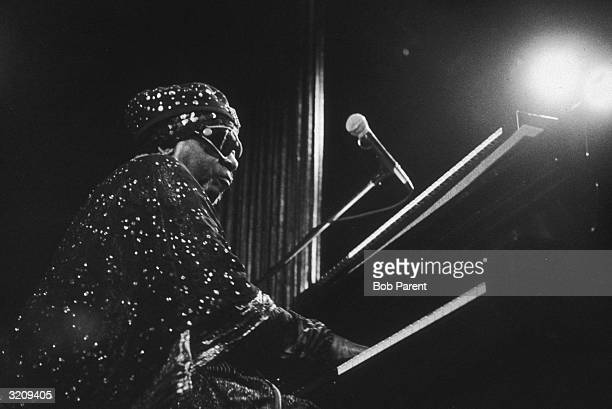 Musician Sun Ra plays the piano while wearing a bejeweled outfit and wraparound sunglasses New York City