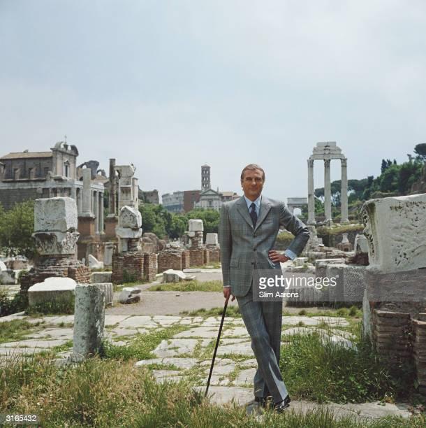 Prince Raimondo Orsini d'Aragona stands in the ancient Roman forum wearing an elegant suit by tailor SaviniBrioni