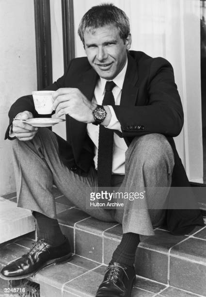 American actor Harrison Ford sits on steps smiling while holding a teacup and saucer