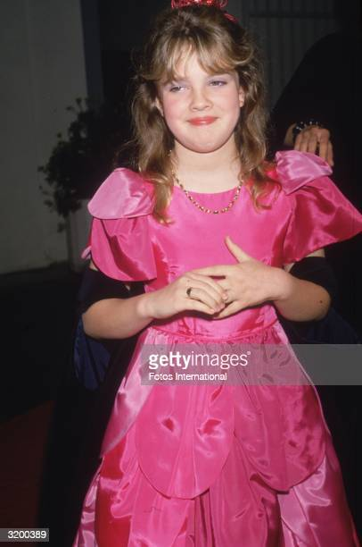 Child actor Drew Barrymore wearing a bright pink gown and smiling
