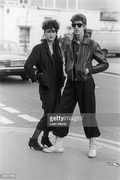 Couple with eighties hairstyles and outfits. The woman wears all black with heeled ankle boots and lace tights, he is wearing wide trousers and has a...