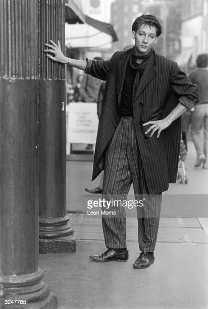 A model wearing a large knee length pinstripe jacket and contrasting wide striped trousers