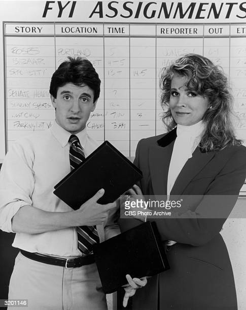 American actors Grant Shaud holding video cassettes and Candice Bergen pose in front of an FYI assignment board in a promotional portrait for the TV...