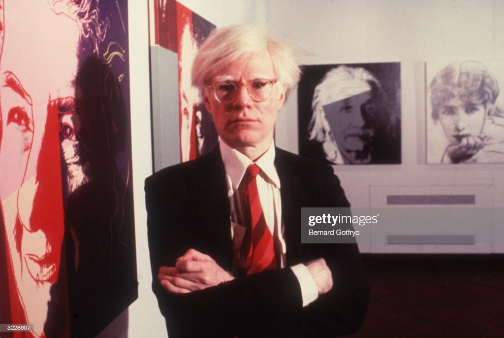 American pop artist Andy Warhol (1928-1987) poses at an exhibition of his lithographs at the Jewish Museum, New York City. Portraits of Golda Meir and Albert Einstein hang on the walls.