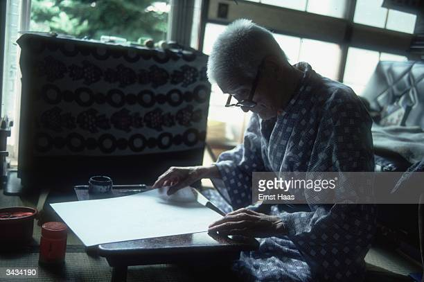 An elderly Japanese poet dressed in a blue kimono lays out a sheet of paper pen and ink are to hand