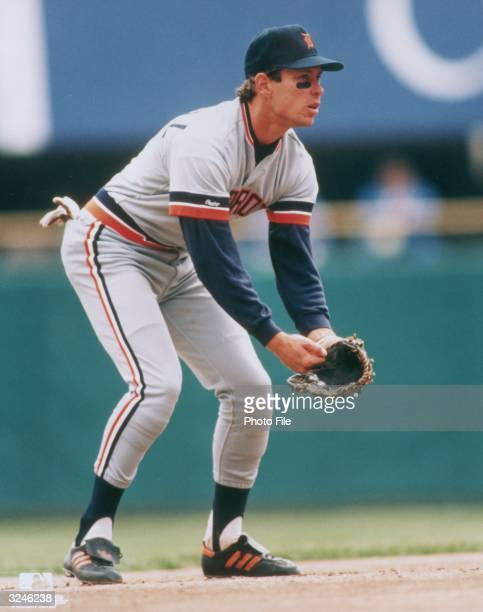 Detroit Tigers shortstop Alan Trammell crouches with his hand by his glove during a baseball game 1980s He wears his uniform