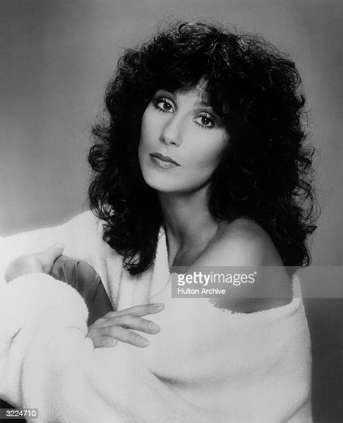 Promotional studio portrait of American actor and pop singer Cher wearing an offtheshoulder cloth robe