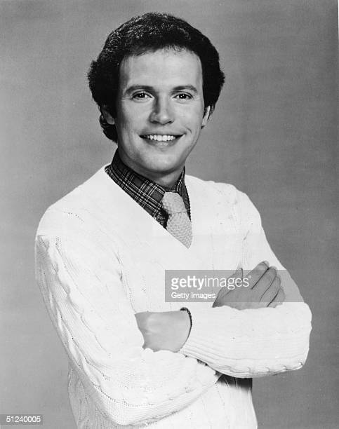 Circa 1985, Promotional studio portrait of American comedian and actor Billy Crystal wearing a white cable knit sweater over a plaid shirt and a...