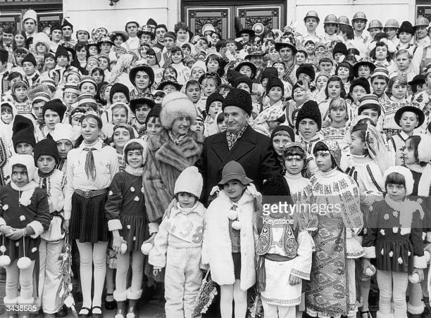 Romanian dictator Nicolae Ceausescu and his wife Elena with a large group of children in national costume