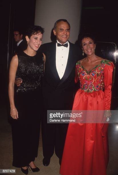 Fulllength portrait of singer actor civil rights activist Harry Belafonte Jr standing with his arms around his daughter actor Gina dressed in black...