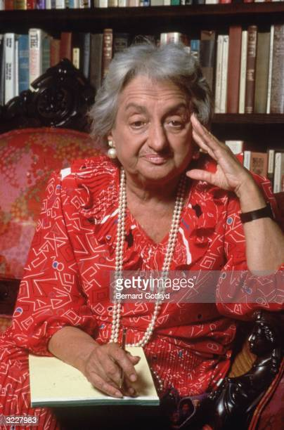 Portrait of American feminist writer Betty Friedan author of the 'Feminine Mystique' wearing a red dress and holding a pen and a legal pad on her lap