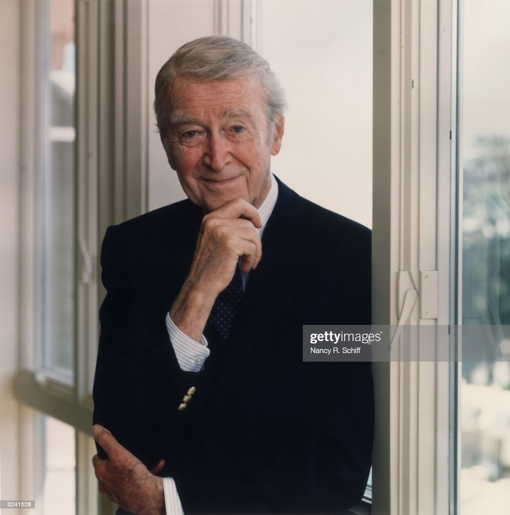 Portrait of American actor James 'Jimmy' Stewart (1908 - 1997) holding one hand to his chin and smiling. He is leaning against a window.