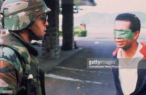 An American soldier stands in the street with a blindfolded Panamanian prisoner during the United States invasion 'Operation Just Cause' to oust...