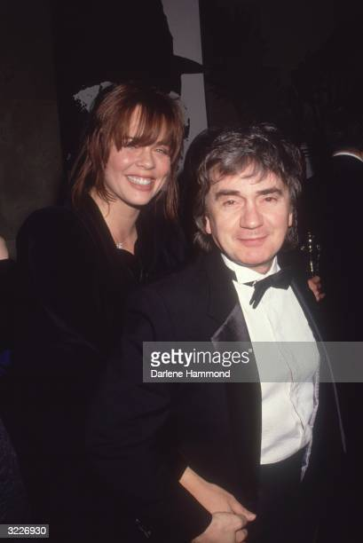 British actor Dudley Moore walking with his third wife Brogan Lane at an awards show