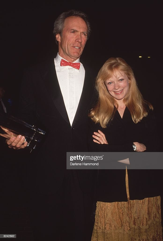 American actor and film director Clint Eastwood and his companion, American actor Frances Fisher, at a formal event. Eastwood is wearing a black tuxedo and a red leather bow tie. Fisher is wearing a black jacket and a marigold lace skirt.