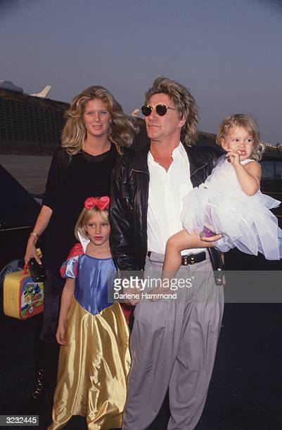 British rock star Rod Stewart standing in an airport parking lot holding hands with his daughter Ruby and carrying his daughter Renee at his hip as...