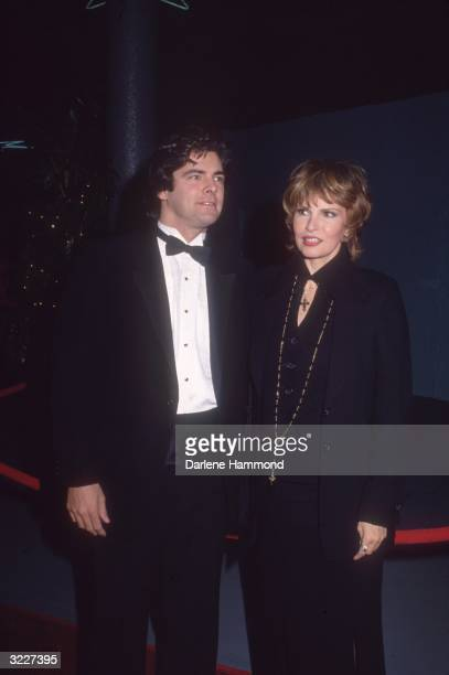 American actor Raquel Welch standing with her son Damon James Curtis Welch is dressed in a long black dress with a gold chain Her son is wearing a...