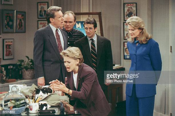 American actors Charles Kimbrough Joe Regalbuto Grant Shaud and Candice Bergen watch Faith Ford as she reacts to a cat sitting beside an empty...