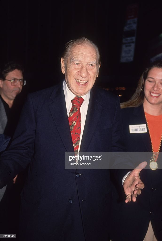 British-born comedian Henny Youngman (1906 - 1998) smiles as he holds his hand out in front of him as if to shake a someone's hand. He is wearing a dark suit and a red tie printed with violins.
