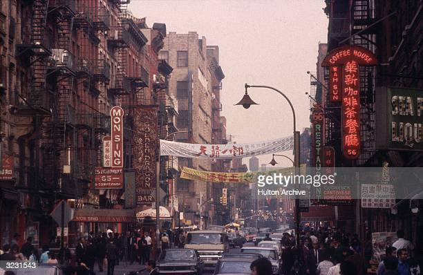 Canal Street with crowded sidewalks and Chinese banners hanging over the street Chinatown New York City Neon restaurant signs advertise Cantonese and...